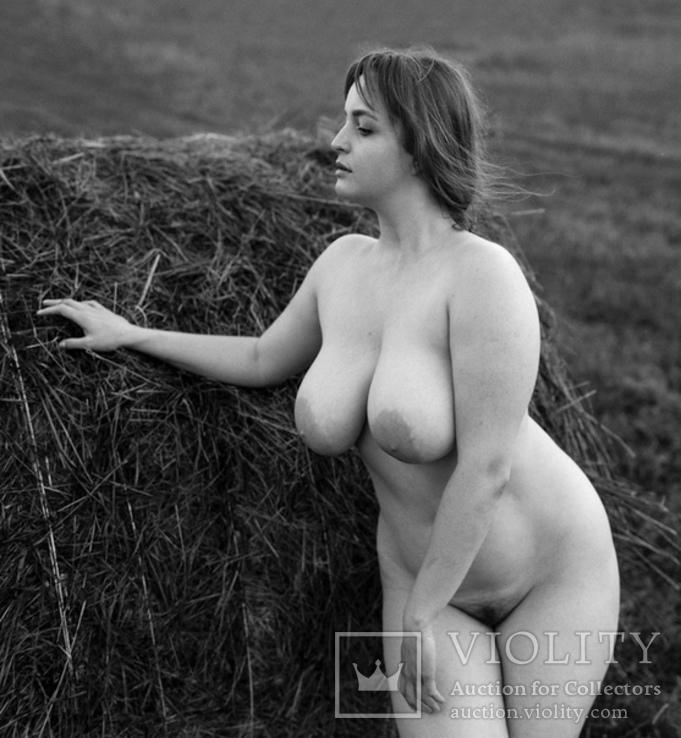 Девушка стоит возле стога сена.