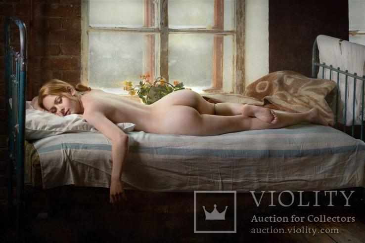 Блондинка спит на кровати у окна.