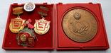 Юбилейные знаки, медали и настольная медаль завода Большевик