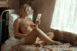Красивая блондинка читает открытку на кровати, фото №2